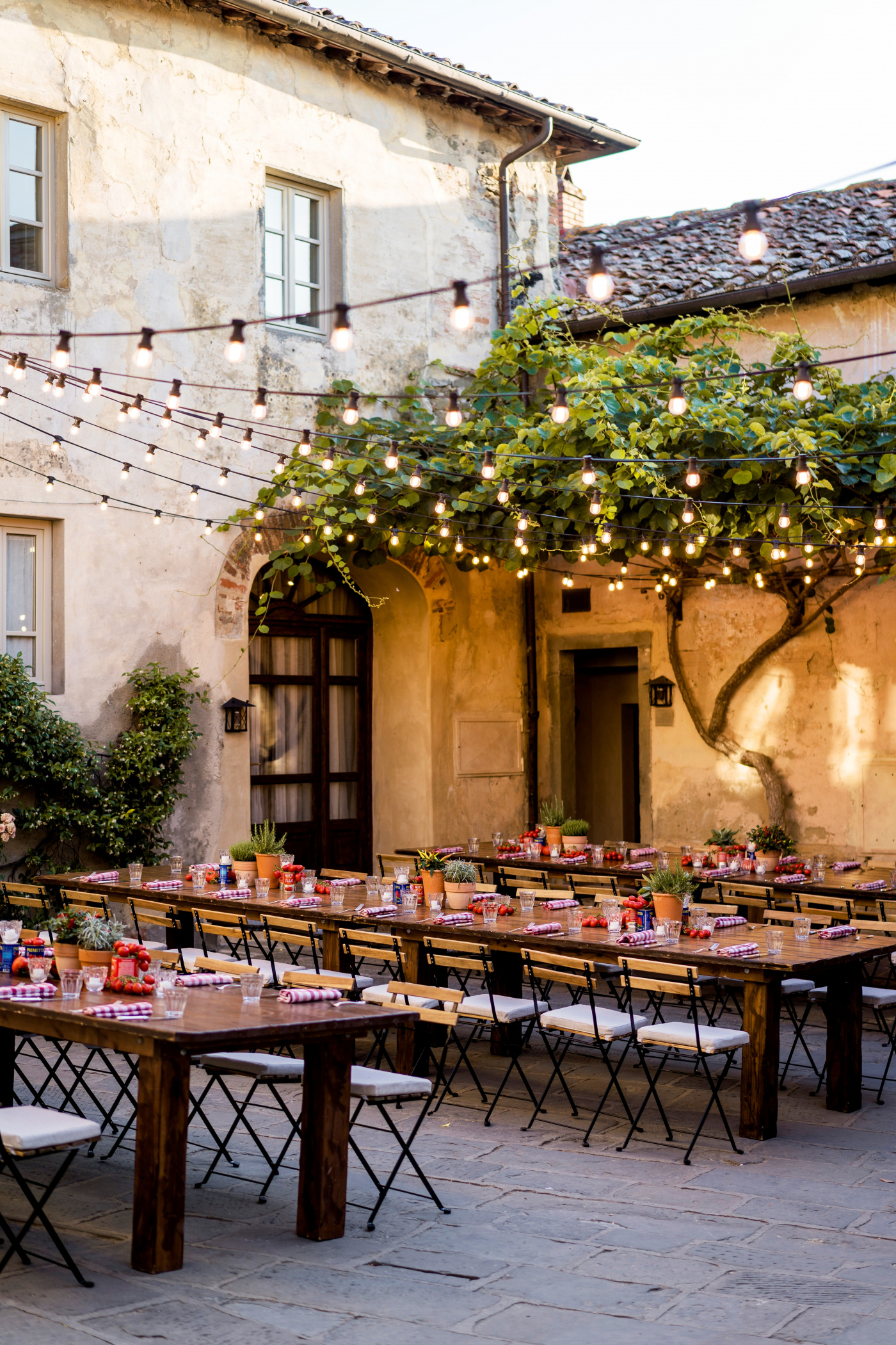 wooden tables and bulb lights for 50th birthday party in tuscany