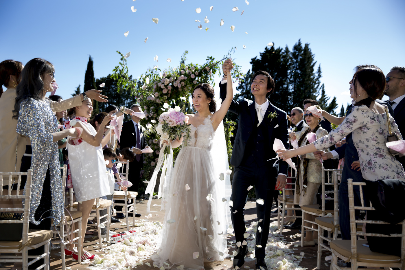 Bride and groom along the ceremony aisle with petals