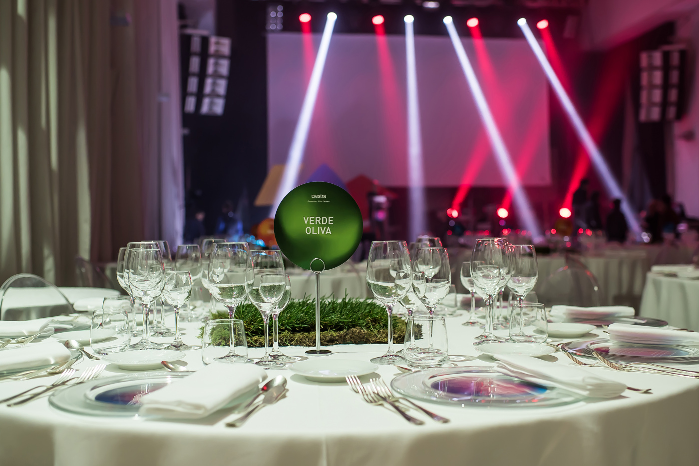 light design for event in rome with round table decored with grass