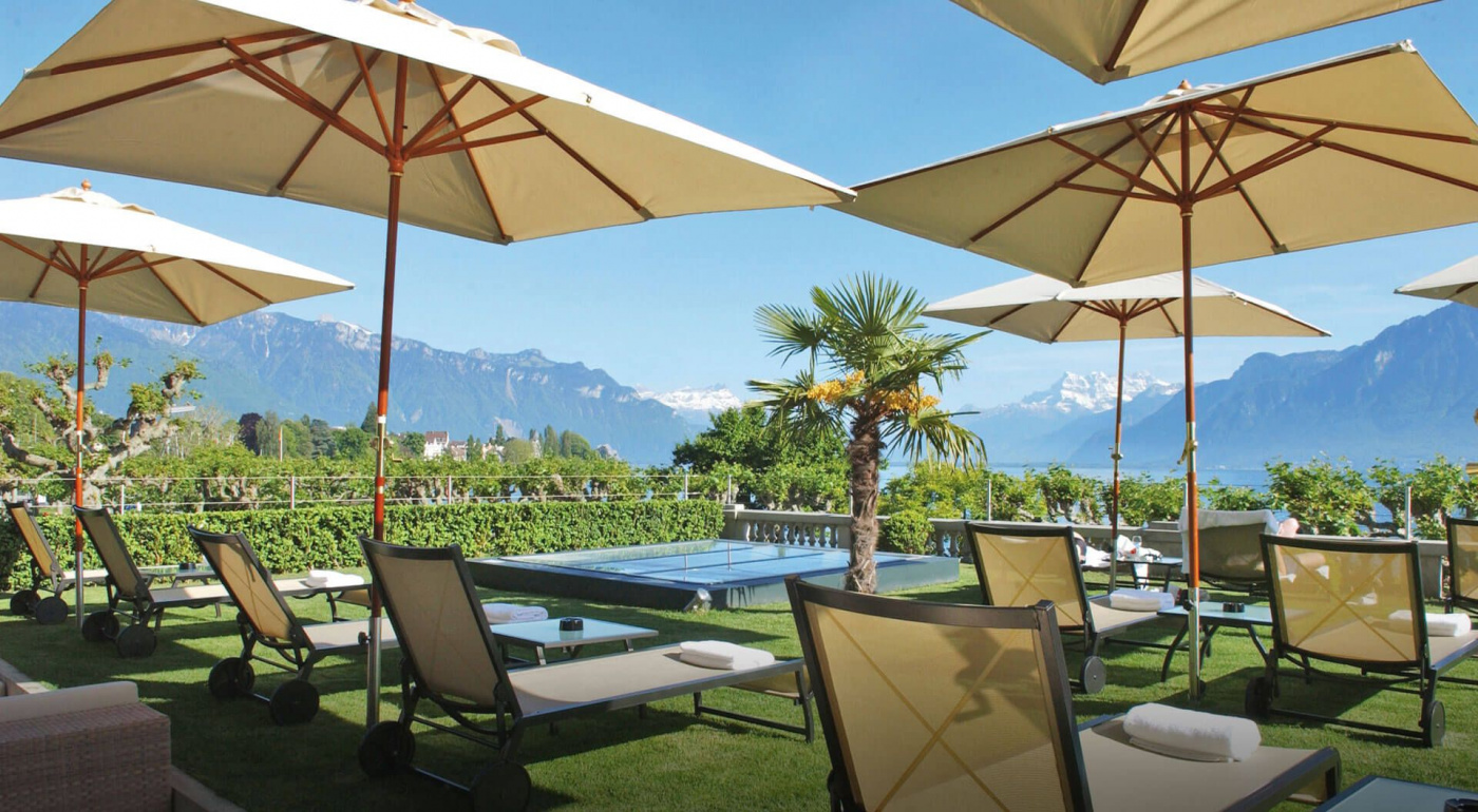 Pool garden with umbrellas and sunbeds in a luxury venue in Switzerland